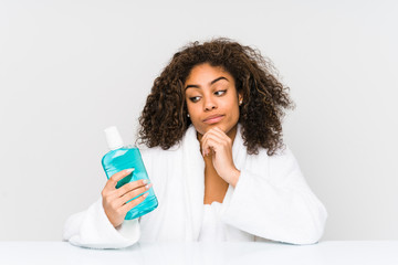 Young african american woman holding a mouth wash looking sideways with doubtful and skeptical expression.