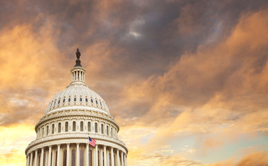 US Capitol dome with American flag and dramatic sky behind