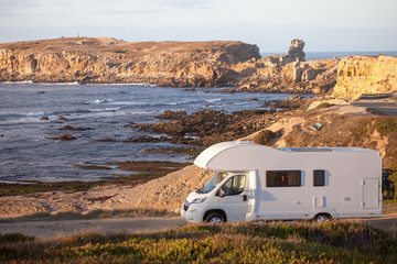 Vacation and travel in caravan.Camper van motor home on seaside road with a sunset