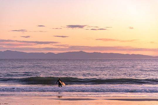 Surfer entering the ocean at sunset