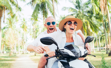 Smiling in love couple travelers riding motorbike under palm trees in their island vacation Fototapete