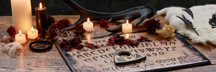 Mystic ritual with Ouija and candles. Devil's board concept, black magic or fortune telling rite with occult and esoteric symbols.