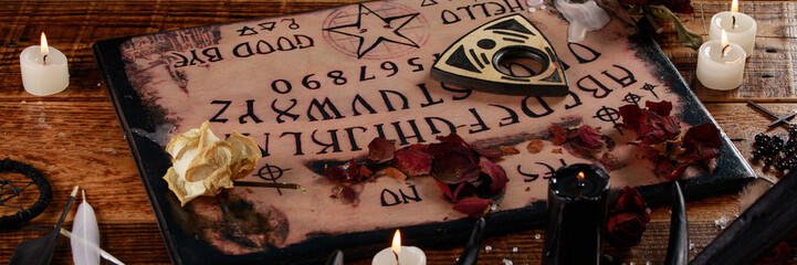 Talking board and planchette, also known as Ouija board, used for communicating with the dead and other spirits. The atmosphere of black art with candles and horns of the animal.