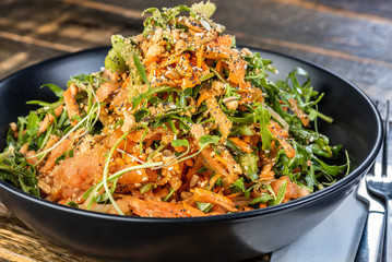 A serving of Papaya Salad with Rocket, Coriander, Roasted Peanuts and Vietnamese Nuoc Cham in a dark plate on a wooden table.
