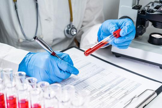 Blood test tubes. Senior female scientist examining blood test tubes at her laboratory dna testing