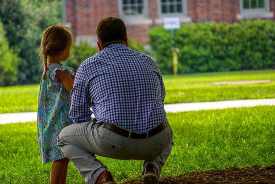 Rear View Of Father Crouching While Daughter Standing On Field