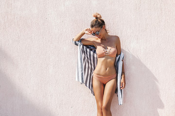Slim woman in beige bikini and striped shirt posing against pink wall in summer sunny day