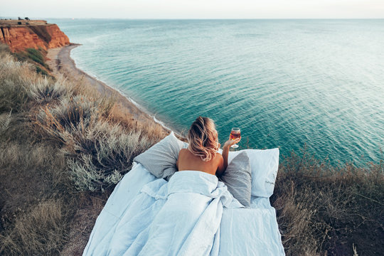 Woman enjoying view on beach landscape while relaxing in bed in sunset on the edge of Earth