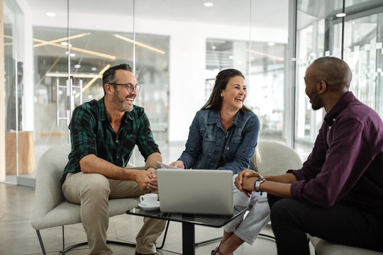 Candid real meeting of diverse successful business team smiling and socializing