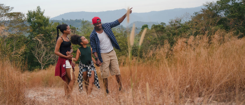 african american family having fun traveling and camping together in natural forest and park