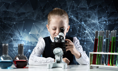 Little scientist looking through microscope