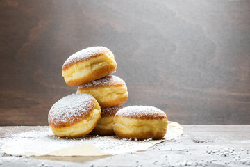 In de dag Hoogte schaal Close-up of donuts (Berlin pancakes) dusted with powdered sugar served on a rustic wooden table