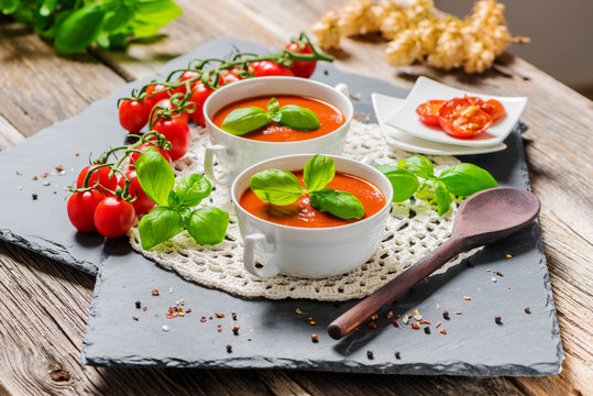 Soup made from fresh tomatoes and herbs, served on a rustic, country-style wooden table