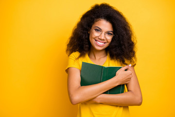 Close-up portrait of her she nice attractive lovely intelligent cheerful cheery wavy-haired girl hugging book enjoying hobby reading isolated on bright vivid shine vibrant yellow color background