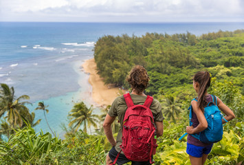 Wall Mural - Hikers couple hiking on Kalalau trail overlooking beach coastal walk two tourists with backpacks walking outdoor in Kauai island, Hawaii summer travel leisure activity active lifestyle.