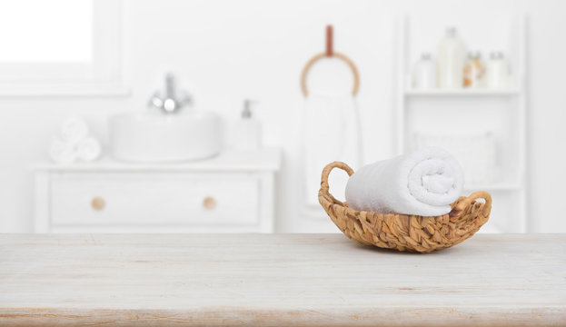 Towel in basket on wooden table over blurred bathroom background
