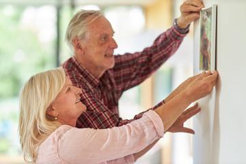 Senioren Paar hängt zusammen ein Foto auf