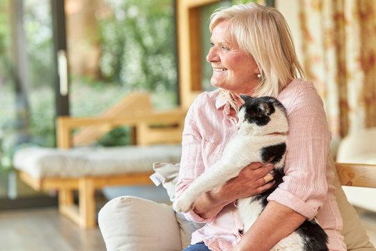Seniorin hält eine Katze auf dem Arm zu Hause