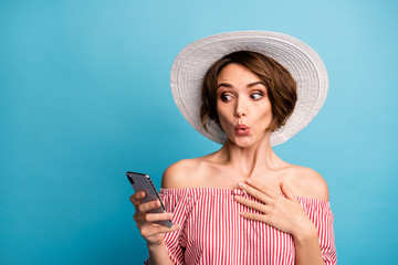 Close-up portrait of her she nice attractive girlish cheerful amazed brown-haired girl using device online shopping service pout lips isolated on bright vivid shine vibrant blue color background