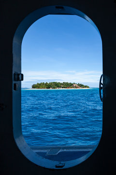 Fijian tropical island view from a boat door porthole, with beautiful blue and turquoise water and clear sky. Beachcomber Resort is part of the Mamanuca Islands , Fiji, Oceania, Pacific Ocean