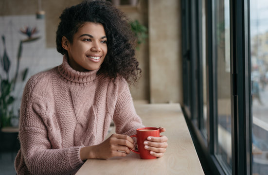 Happy African American woman drinking coffee in modern cafe. Young beautiful girl holding cup of tea, looking at window and smiling