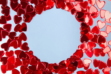 Heart shape confetti arranged into a circle frame on blue background.