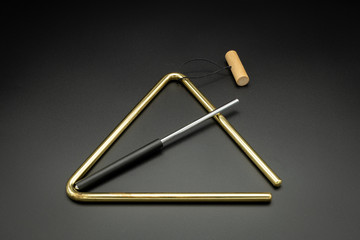 A brass triangle lying on a black underground