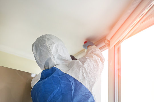 Man wearing protective biological suit and gas-mask due to mers coronavirus global pandemic warning and danger. Worker make disinfection, pest control and mold removal and ventilation at house room
