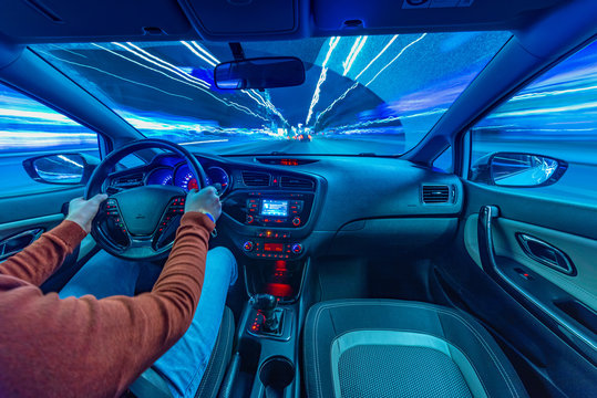 The movement of the car at night in the rain. Hands on the steering wheel. Blur neon lights.