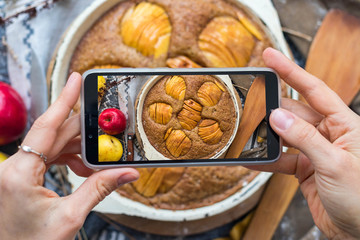 Woman take a picture of apple pie or cake using phone at her kitchen. Vegan healthy dessert. Smartphone food photography