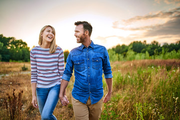 Smiling couple walking through meadow on sunny day and holding hands