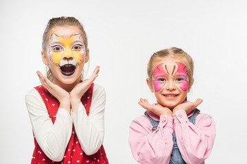 excited friends with cat muzzle and butterfly paintings on faces looking at camera isolated on white