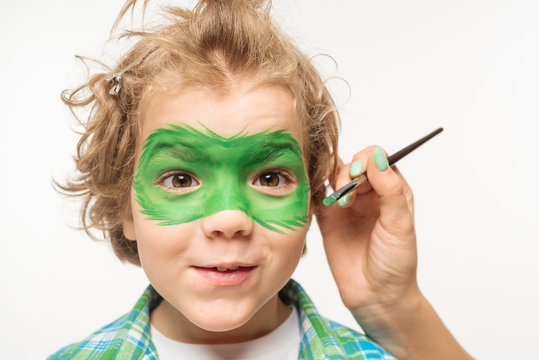 cropped view of artist painting gecko mask on face of shaggy, cheerful boy isolated on white