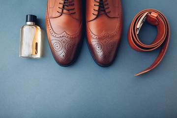Oxford male brogues shoes with accessories. Men's fashion. Classical brown leather footwear with belt and perfume.