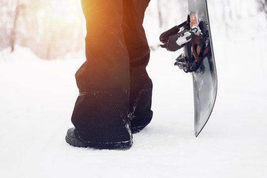 Snowboarder standing with snowboard over winter snow background.