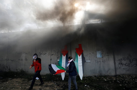 Demonstrators walk after placing on the Israeli barrier representations of maps with the colors of the Palestinian flag during a protest against Trump's Middle East peace plan, in the village of Bilin in the Israeli-occupied West Bank