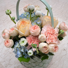 Tuinposter Lelie A bouquet of fresh flowers of roses, anemones and gartensium in a basket on a stone background.