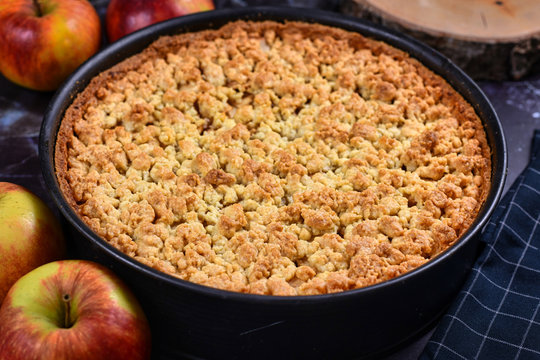 Whole traditional European apple pie with topping crumbles in springform pan