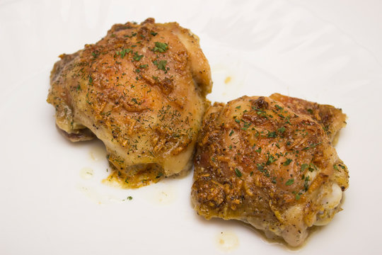 Freshly baked chicken thighs in oven from clouse up on white background
