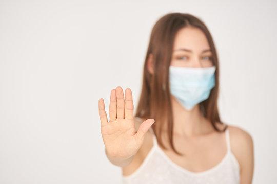 Influenza virus stop gesture. Girl in face mask show deny sign. Hand selective focus. Female blur portrait. Coronavirus sick