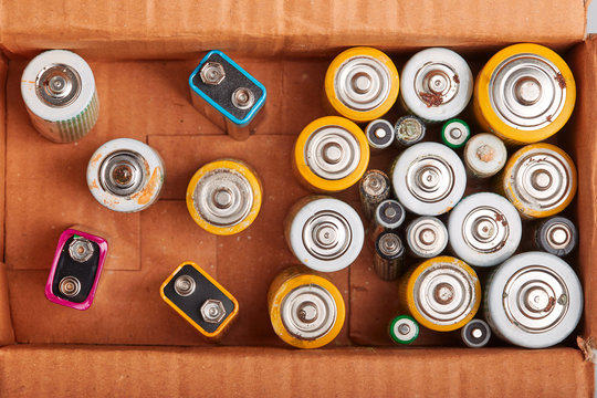 Discharged batteries in cardboard box. Collecting used batteries to recycle. Waste disposal and recycling. Copy space for text