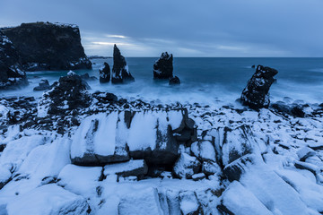 Beach with sea stacks covered in snow in Iceland