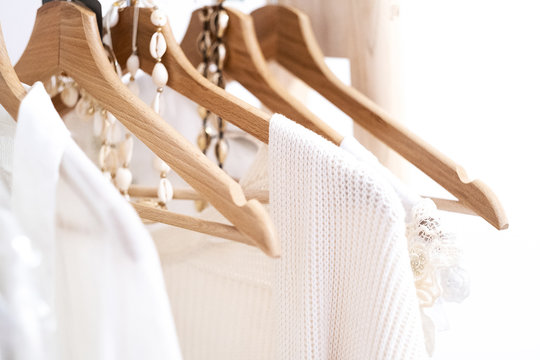 Detail of white clothes hanging on wooden hangers in a fashion store.