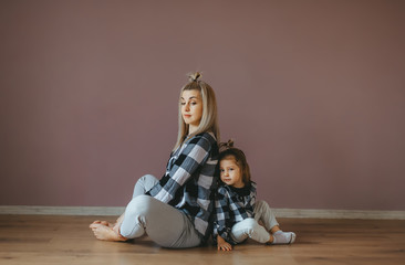 Mother with child practicing yoga in a lotus pose. Horizontal portrait