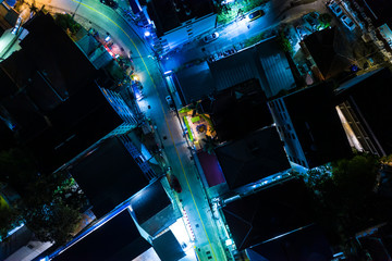 Bright night time illumination with traffic on street. Many motorbike moving on the city road at in the evening time. Aerial Fotobehang