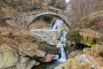 Ancient stone bridge on the Fondo waterfall, in the alpine Chiusella Valley, Piedmont, Italy