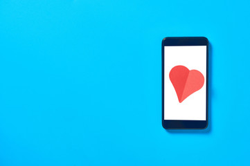 Black smartphone with isolated white screen for text, picture, photo and other graphics and red paper heart lies on blue table. Valentines day and love concept. Space for text. Top view