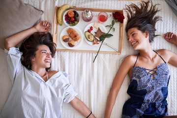 sexy homosexual couple in bed having healthy breakfast on valentines day. Love, Romance and morning concept.
