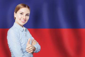 happy woman showing thumb up on Haiti flag background. Travel in