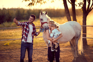 Dad taking a photo with faily and a horse. Family on countryside, sunset golden hour. Freedom...